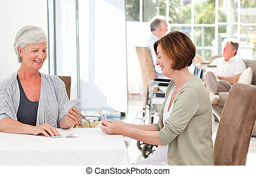 Senior women playing cards while their husbands are talking