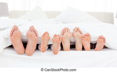 Familys feet in the bed