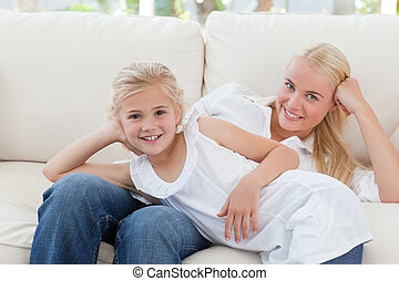 Beautiful woman lying down with her daughter at home