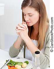 Woman praying at the table