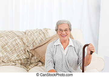 Mature woman sitting on the sofa with her walking stick at...