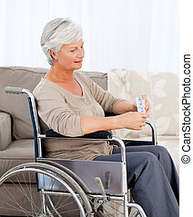 Senior in wheelchair with pills