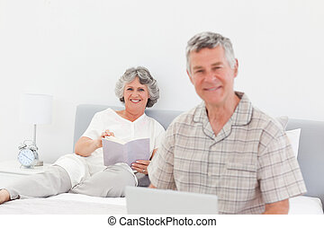 Man working on his laptop while his wife is reading at home