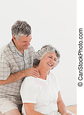 Retired man giving a massage to his wife at home