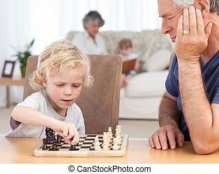 Young boy playing chess with his grandfather at home