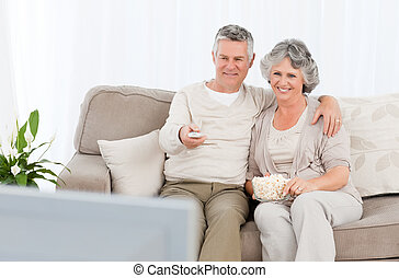 Mature couple watching tv in their living room at home