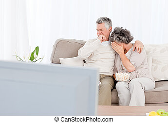 Mature couple watching tv in their