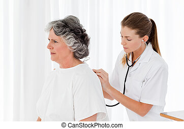 Pretty nurse taking the heartbeat of her patient
