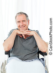 Man on his wheelchair looking at the camera at home