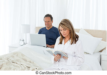 Senior looking at his laptop while her wife is reading -...