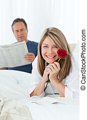 Happy woman with her rose while her husband is reading a newspaper at home