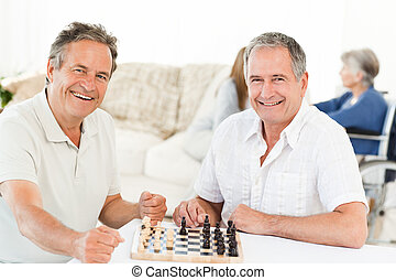 Men playing chess while their wifes - Men looking at the...
