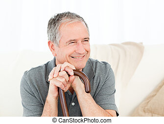 Mature man with his walking stick on his bed at home