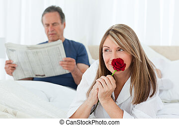 Happy woman smelling her rose while her husband is reading a newspaper at home
