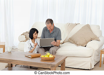 Mature man with his nurse looking at the laptop at home