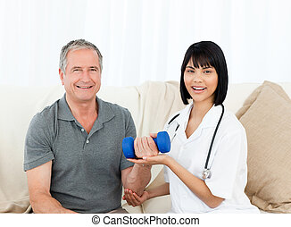 Nurse helping her patient to do exercises at home