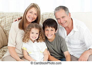 A happy family on their sofa looking at the camera at home