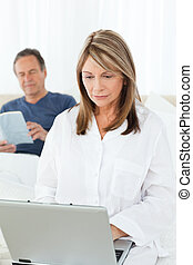 Woman looking at her laptop while her husband is reading on...