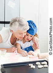 A little girl baking with her grandmother - A little girl...