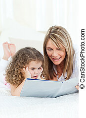 Young girl reading a book with her grandmother