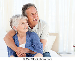 Senior couple hugging on their bed at home