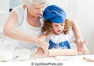 A little girl baking with her gran - A little girl baking...