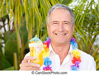 Mature man drinking a cocktail under the sun