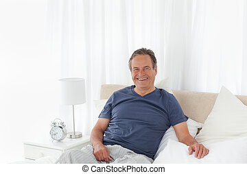 Man  lying down on his bed at home