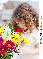 A little girl smelling  flowers