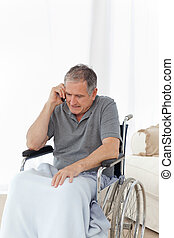 Senior in his wheelchair phoning at home
