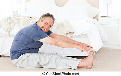 Mature man stretching in his bedroom