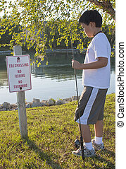 "Young boy reading the ""No Fishing"" sign"