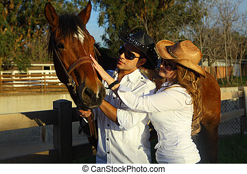 Couple with brown horse - Couple petting their beautiful...