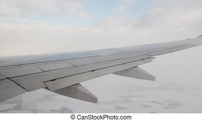 Winter flight. - Detail of passenger jet wing. Snowy winter...