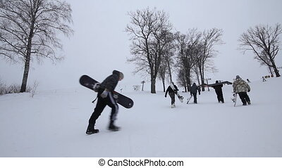 Company snowboarders up the hill