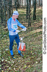 The sportsman on sport orienteering competitions looks a map...