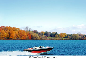 power boating on an autumn lake on a sunny day