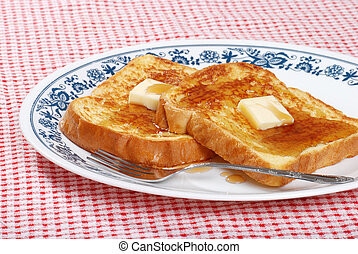 french toast syrup and fork on red and white checkered...