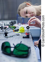 female scientist doing research in a quantum optics lab...