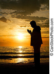 Man Standing at the Ocean Praying - A silhouette of a man...