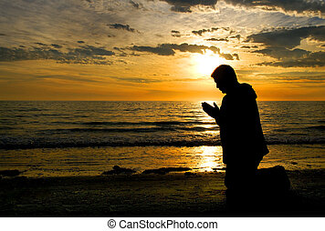 Praying to God - A man kneeling and praying at the ocean...
