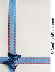 Textured ribbon over cream textured paper with butterfly...
