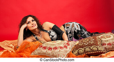 Beauty woman lay on pillow and smile in harem