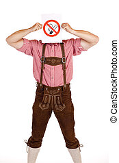 Bavarian man in lederhose holds no-smoking-rule sign in...