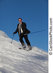 Man in business sute on ski going down