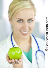 Smiling Woman Doctor in Hospital Holding Green Apple -...