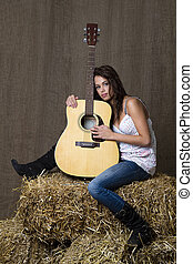 Young musician - young brunette girl leaning on accoustic...