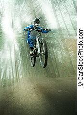 light jump - mountain biker jumping through the forest with...