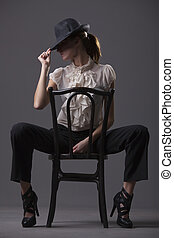 female dancer with hat sitting on the chair over grey...