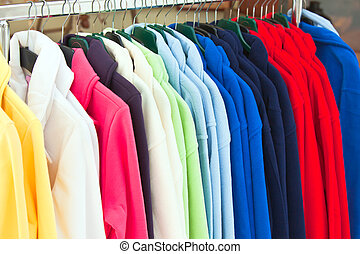 multicolor sport shirts hanging in store - Colourful Textile...